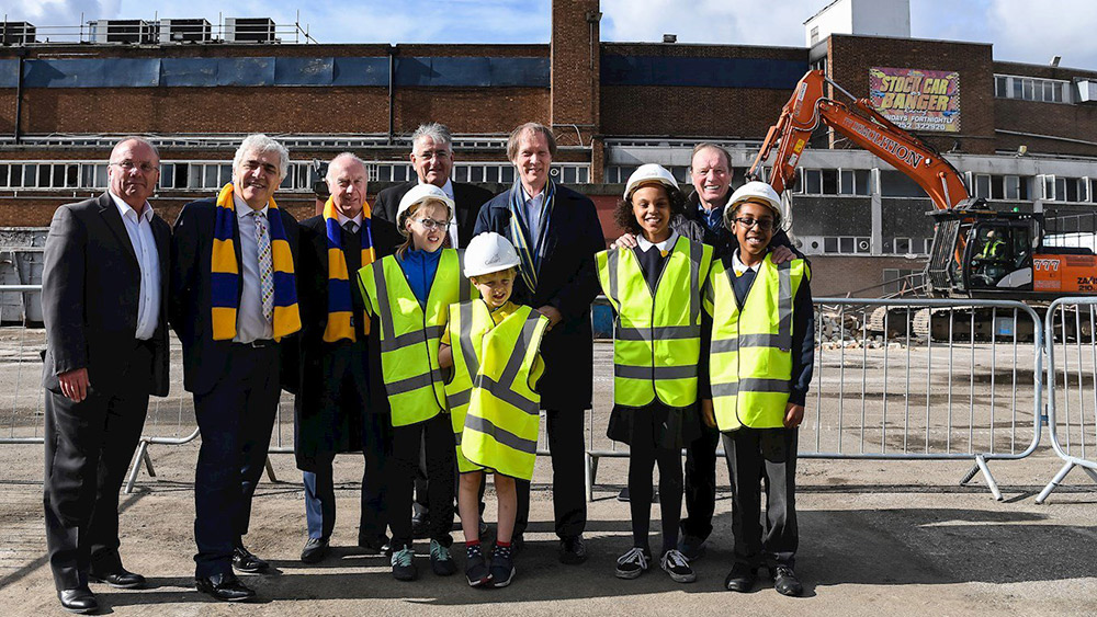 Ceremony to mark the beginning of demolition work at Plough Lane, March 2018 Left to right: Mike Watson, Architectural Director at Galliard Homes, Merton Council Leader Stephen Alambritis, former Wimbledon player Ian Cooke, Victor Clinton-Dove, Director of Development at Catalyst, AFC Wimbledon Chief Executive Erik Samuelson, and former Wimbledon manager Dave Bassett with children from the Foundation's Wimbledon Park Development Centre and pupils from Smallwood Primary School in Tooting.